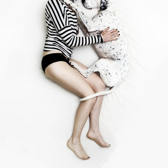 Woman and Dalmatian mongrel lying on white bed sheet - ONF000631