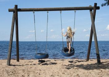 Sweden, Vastra Gotaland County, Lake Skagern, girl on swing - JBF000212