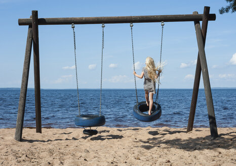 Sweden, Vastra Gotaland County, Lake Skagern, girl on swing - JBF000212
