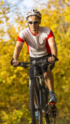 Man riding mountaimbike in autumnal forest - STSF000642