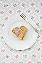 Dish of heart shaped waffles sprinkled with icing sugar on patterned cloth - LVF002373