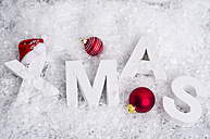 Red Christmas baubles and white letters building the word 'XMAS' lying in artificial snow - ODF000892