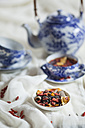 Bowl of black spice tea with dried Goji berries, Lycium barbarum, on white cloth - SBDF001476