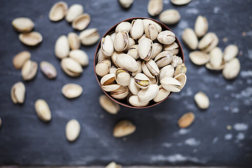 Bowl of roasted and salted pistachios on slate - SBDF001512