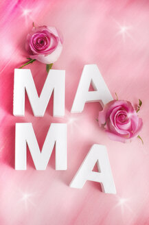 Two rose blossoms and white letters building the word 'MAMA' on pink background - ODF000898