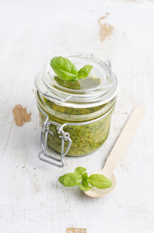 Preserving jar of fresh pesto, wooden spoon and basil leaves on white wood - ODF000901