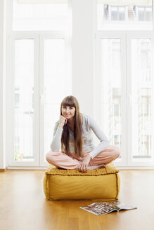 Relaxed woman on ottoman at home - FMKF001376