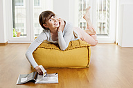 Relaxed woman reading magazine on ottoman at home - FMKF001382