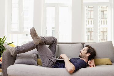 Relaxed man lying on couch using laptop - FMKF001387
