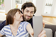 Happy couple taking selfie at home - FMKF001391