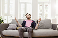Disappointed man with pink baby shirt on couch - FMKF001394