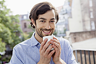Portrait of smiling man on balcony drinking coffee - FMKF001419