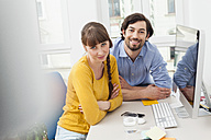 Portrait of smiling couple in home office - FMKF001442