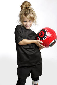 Portrait of blond girl with red soccer ball wearing football sportswear in front of white background - GDF000623
