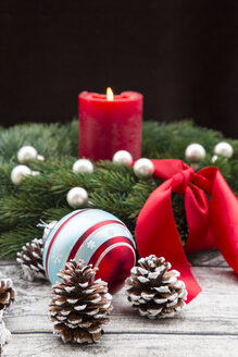 Advent wreath with lighted red candle, Christmas bauble and fir cones on wood - LVF002397