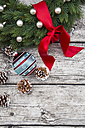 Advent wreath with red bow, Christmas bauble and fir cones on wood - LVF002398