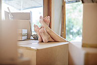 Couple moving house, feet on a box - ZEF002848