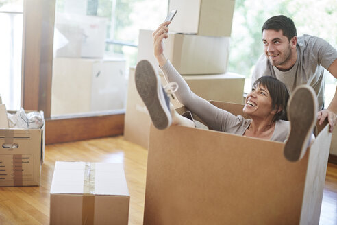 Playful couple moving house sitting in a box taking a selfie - ZEF002855