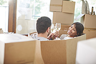 Couple moving house sitting in a box and clinking wine glasses - ZEF002857