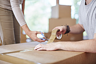 Couple moving house closing a box - ZEF002865