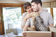 Couple moving house sharing a moment with the dog - ZEF002912