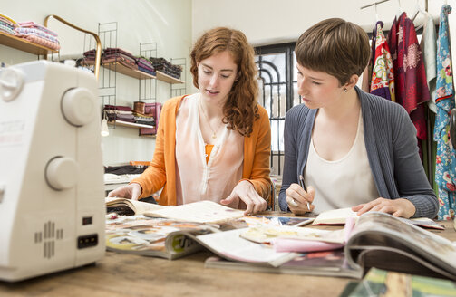 Two female fashion designers at her work desk - DISF001121
