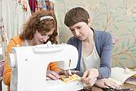 Two female fashion designers working together at their studio - DISF001132