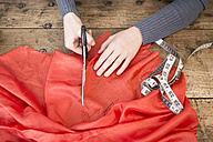Hands of young woman cutting red cloth with scissors - DISF001151