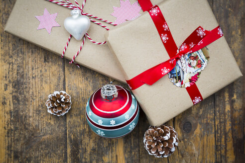 Wrapped Christmas presents, Christmas bauble and fir cones on dark wood - LVF002408