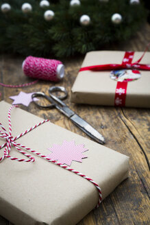 Wrapped Christmas presents and scissors on dark wood - LVF002406