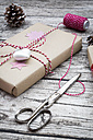 Wrapped Christmas presents, scissors, ribbon and fir cones on wood - LVF002403