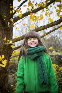Portrait of grinning girl wearing green scarf and green jacket - LVF002410
