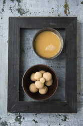 Bowl of butter tea, bowl of Tsampa balls and black picture frame on grey ground - MYF000728