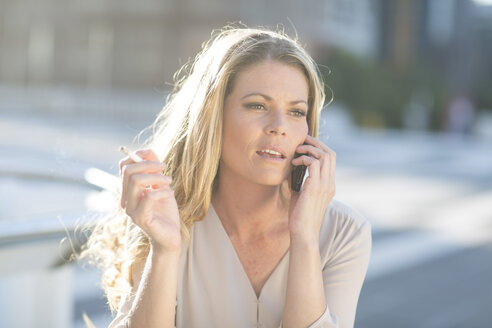Woman with cigarette on cell phone - ZEF001575