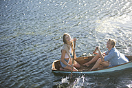 Happy young couple in a rowing boat on a lake - ZEF002336