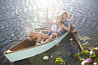 Playful young couple in a rowing boat on a lake - ZEF002340