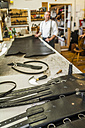 Vaulting belts, tools and leather on working table in saddlery - TCF004363