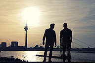 Germany, North Rhine-Westphalia, Duesseldorf, two man looking to Rhine tower and Rhine river at sunset - FRF000140