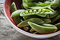Bowl of whole and opened peasecods of snow peas - SARF001123
