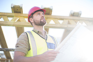 Construction worker holding plan at construction site - ZEF001657