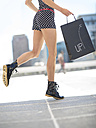 Woman with shopping bag wearing black patent leather boots - ZEF002103