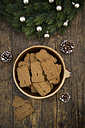 Bowl of almond biscuits, fir cones and decorated fir branch on wood - LVF002436