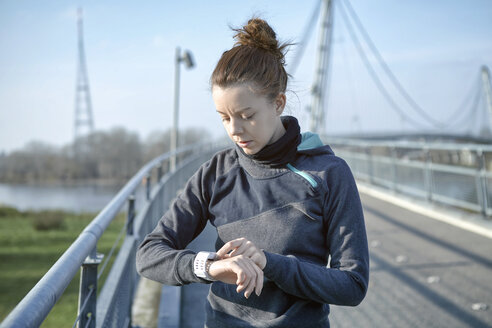 Young woman checking heart rate monitor after jogging - SEGF000069