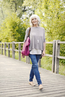 Portrait of smiling white haired senior woman walking on a wooden boardwalk - VRF000135