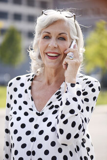 Portrait of smiling senior woman wearing sunglasses telephoning with smartphone - VRF000128