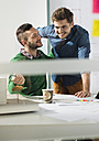 Two smiling young men in office with architectural model - UUF002787