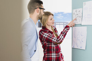 Young man and woman in office discussing mind map - UUF002829