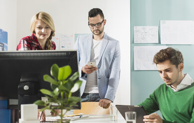 Three young people in office with computer monitor - UUF002832