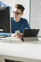 Young man at desk with computer, digital tablet and cell phone - UUF002842