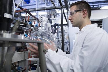 Chemist in lab holding round bottom flask - SGF001203